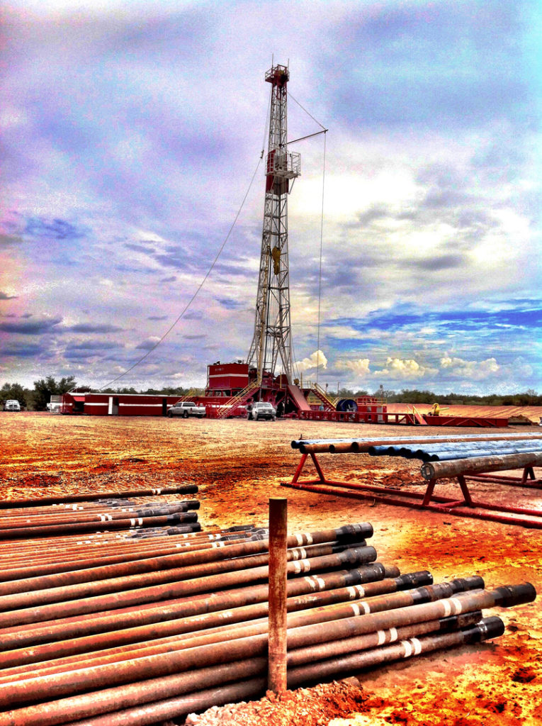 Drilling location with oil rig operation and oil pipes.