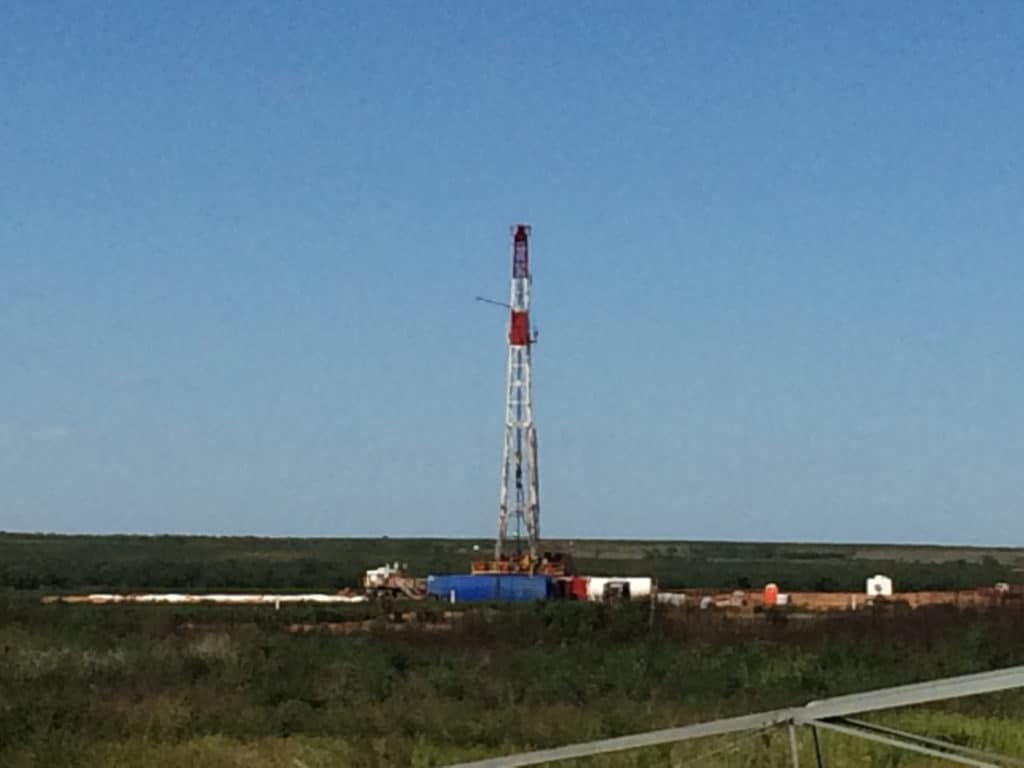 Distant view of oil drilling rig operating in a Texas field.